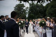 Bride and groom coming down the aisle at an outdoor ceremony at Swynford Manor