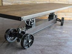 Shown with a 12' x 48 reclaimed boxcar oak top  Natural Steel or Rust finish (natural steel shown)  12.5  handmade casters  4 wheel steering and brakes for moving it around and keeping it in place  Height adjusts from 30 - 42 (dining to bar height) via the two 5 ton screw mechanisms  960 lbs weight for 12' version (approximate)  Fully customizable, and hand built from scratch i nour Phoenix shop