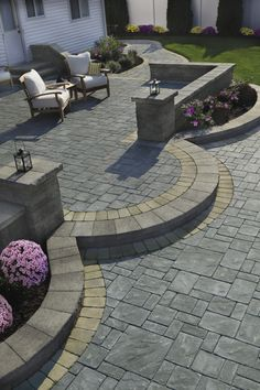 @cambridgepavers multi-level patio with seating wall and planting area.