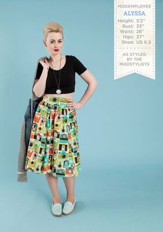 The ModStylists love styling the gorgeous ModCloth employees! In this outfit: Flair for the Fantastic Skirt in Cameras, Cat Your Eye on the Time Necklace, Around Downtown Jacket, On Crop of the World Top in Black, Loafer and Over Flat in Spearmint #retro #camera #print #croptop