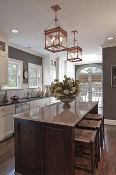 Grey walls, white cabinets, brown floors - I love how warm this all looks together  Large pendants over a different colored island.