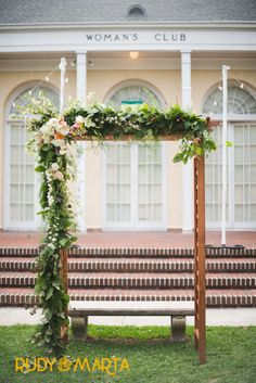 a varnished wood arbor for the wedding ceremony is asymmetrically dressed with lemon leaf, seeded eucalyptus & fern garland with white roses, peach campanella roses,white lisianthus, button chamomile, pink larkspur, white spirea & peach stock peppered throughout