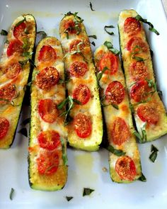 Slice the zucchini in half. Slice off the bottom to keep in stable. Brush with olive oil and top with garlic or garlic powder. Top with sliced tomatoes, salt and pepper to taste. Use mozzarella cheese, Parmesan cheese or mixed blend.. Bake 375 for 20 to 30 minutes until soft.