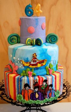 "Beatles ""Yellow Submarine"" theme cake for a 64th birthday! Customer was a huge Beatles fan and loved to sing ""when I'm 64!"" naturally, I went with a Beatles theme for his cake. I hand painted and drew the Fab 4 and the Yellow Submarine. I chose psychedelic colors to match the movie posters. The cake itself was my signature chocolate dulce de leche flavor!"
