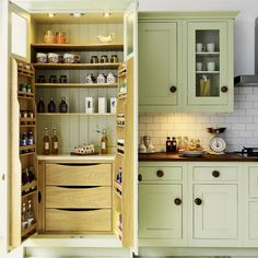 Lovin' these Shaker-style cabinets with wood knobs, as well as the bead-board backing in the pantry.