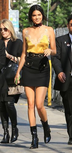 Kendall Jenner in a yellow lace Gucci top, black miniskirt, choker and boots