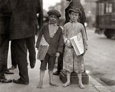 """May 1915. """"Nine-year-old newsie and his 7-year-old brother 'Red.' Tough specimen of Los Angeles newsboys."""" Photo by Lewis Wickes Hine"""