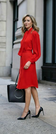 classic bright red tie neck silk tie waist midi dress with pleated blouson sleeves and classic tote bag and pumps.