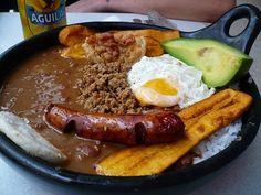 """La Bandeja Paisa es un plato típico también conocido como """"bandeja de arriero"""" o """"bandeja montañera"""", tradicional de la cocina antioqueña (Antioquia, el Viejo Caldas o Eje Cafetero Caldas, Quindío y Risaralda), su característica fundamental es su enorme abundancia, tanto en cantidad como en variedad de alimentos, de tal modo que la bandeja paisa solo cabe servirla en platos grandes llamados """"bandejas""""."""