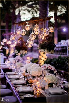 Breathtaking destination at Esperanza Resort in Cabo San Lucas! Features a chuppah and table settings with clear glass hanging votives and lots of white florals. Photos by chrispluslynn.com