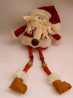 Boneco de Papai Noel para enfeite. Confeccionado em tecido 100% algodão, enchimento siliconado, miçangas e botão em madeira e acrílico, bota em feltro, pernas feitas com carreteis de linha pintados com tinta á base de água, óculos em arame galvanizado. <br> <br>Dimensões: <br> Sentado: 17 cm x 16 cm x 10 cm <br> Esticado: 37 cm x 16 cm x 10 cm