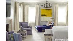 """The master bedroom in a Scarsdale, New York, house has neutral colors with purple and blue accents. An abstract painting, """"looks like the sun rising. Waking up happy is what this master bedroom is all about,"""" designer Pat Healing says.   - HouseBeautiful.com"""