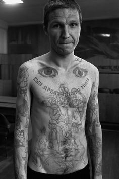 The eyes on the top of the chest signify 'I can see everything' and 'I am watching'. Text across the chest reads 'Son of the criminal world'. This photograph shows tattoos in a combination of old and new styles. In the 'new' style a large number of almost random images on the convict's body. In the 'traditional' style there is one large central tattoo on the chest, filling as much space as possible.