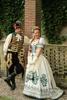 Victorian hussar uniform and cream silk bustle gown with beetle wing embroidery. Costumes made by Angela Mombers