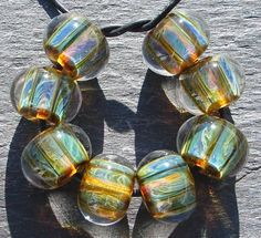 Bead Goodies: Lampwork Frit, using Iris Gold for faux boro. I made these with a base of Effetre Black, then applied dots made with Effetre Transparent Light Brown and Gold Iris frit, melted flat and then encased.