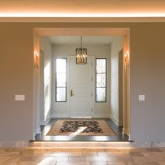 The entry foyer features a hanging chandelier and adjacent adorning sconces with under-lit step into the main living room. Vaulted ceiling with recessed can lights and surrounding crown lights bring a warm feel to this room featuring stone fireplace and windows facing the backyard.