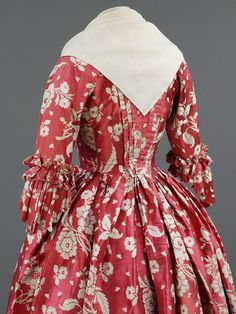 Detail back view, robe à l'Anglaise, Great Britain, fabric: 1740-1749, robe: 1760-1769. Woven rose-red silk with trails of ivory flowers and floral sprays. The fabric, a type of silk known as gros de tours, dates from the 1740s, but the gown itself has been remade into the style of the 1760s.
