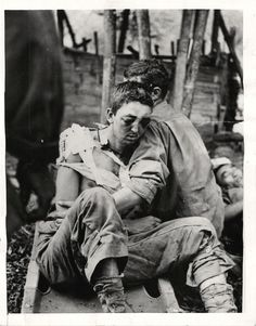 1944- Wounded U.S. soldier is helped from stretcher by fellow soldier after participating in the battle of Hukawng Valley in Northern Burma.