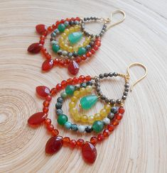 Bold, colourful and effortlessly bohemian, Macarena beaded hoop earrings are your best companion to a party! Light as a feather and with just the right amount of sparkle, they will surely make a statement when you wear them. Three parallel round hoops featuring: carnelian faceted