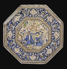 A LARGE QAJAR OCTAGONAL TILE, PERSIA, 19TH CENTURY     of octagonal form, moulded and painted in underglaze cobalt blue, pink, olive green, brown and yellow, featuring a mythological scene with a turbanned man in flight above two grotesque crocodile-headed figures, one with monstrous crocodile-headed arms, bordered by a thin band of scrolling palmettes, with a larger mouldedband of interlocking lotuses and palmettes  35.9cm.