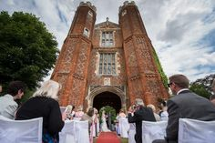 Leez priory wedding photographer wide angle of gate house outdoor ceremony clouds beautiful