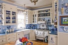 French country kitche. White and blue kitchen. Antique replica stove in white.