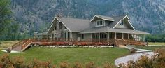Custom chalet-style modular home in the mountains with large wrap-around deck and stone chimney.