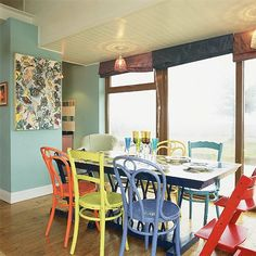 Colourful dining room  This colourful open-plan dining space is ideal for a fun-loving family with young children. The room benefits from huge glass walls looking out to sea and the dining table, retrieved from a skip, plus mismatched, painted chairs are perfectly positioned to enjoy the view.