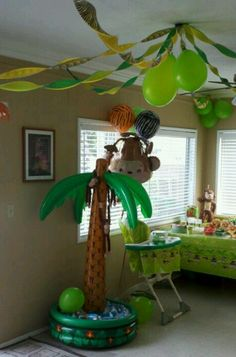 My son's first birthday party, safari style. Inflatable palm tree cooler, monkey pinanta, safari balloons, streamers, jungle decorations, decorated highchair.