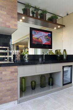 O espaço gourmet, aberto para a varanda e integrado ao living, conta com churrasqueira, bancada e adega. A TV instalada sobre o painel espelhado é o destaque do ambiente.