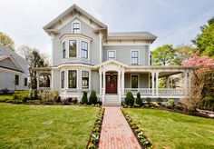 Traditional Exterior of Home with double-hung window, Glass panel door, Wrap around porch, Raised beds, Deck Railing, Pathway