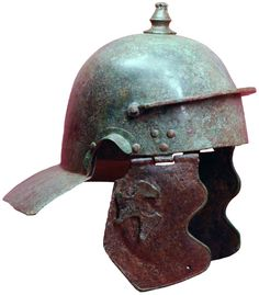 """Roman bronze Weisenau type helmet with an unknown  variation: two iron cheekpieces with copper edging and the remainder of a  figural brass decoration on the right cheek piece. The helmet belongs to a relative small group of Weisenau helmets without """"eyebrows"""" and articulated horizontal ribs at the back of the skull, the neckguard is undecorated but it features a singular hole at its very center. The frontal protective bar carries a three letter inscription (underside). Dated: Mid - 1st c…"""