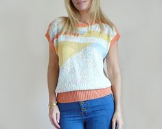 Adorable vintage 80s pastel knit top sweater featuring a geometrical pattern in shades of pale blue, yellow, cream and orange. Bouclé textured knit with ribbed colar, sleeves and waistband. Loose boxy shape with short dolman sleeves.  DETAILS: Era: 1980s Material: Cotton / Acrylic blend Label: no label  MEASUREMENTS: Best fits: S-M-L (Depending on desired fit) Shoulders: Free Bust: 19 Waist: 14 to 18 (stretch) Length: 20 - For reference, model is a size 6/Small with bust 34B  CONDIT...