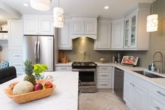 """As seen on Property Brothers Season 4 Episode 26 """"Jessica & Chase"""".  Featured on the kitchen walls/backsplash is Color Wave Whisper Green CW12 Straight-Joint Mosaic Glass Tile. The floor is Exquisite Chantilly 12x24 Glazed Porcelain tile in a herringbone pattern"""