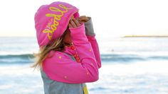 Woman pink hoodie with dots - crazy sunset colors walking down the beach