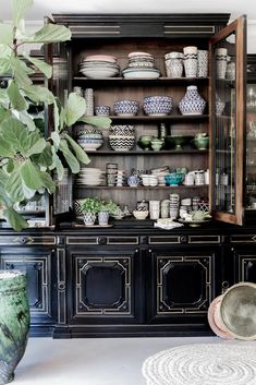 Lovely oversized dark shop cabinet filled with colorful pattern dish ware. I love shop cabinets for a large living room.