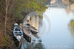 Photo made in three small boats in the river Bacchiglione in Padova in Veneto (Italy). In the image you see, moored to the shore looking towards the coast Paleocopa, three small boats, the one closest to the shore is decorated on top. Complete the image of the green leaves of some branches that extend over the water and the blue sky reflected on the water.