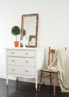 white dresser with caster feet and natural wood chair