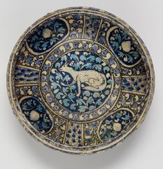 A Sultanabad pottery Bowl   Persia, early 14th Century  of squat inverted pear-shaped form, decorated in underglaze cobalt-blue, turquoise and black outline with a central medallion containing a seated fox, against a reserve of foliage  21.2 cm. diam.
