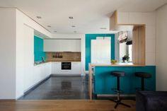 weiße Einbauküche mit Küchentheke und Wandfarbe Türkis