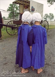 Two amish girls with caps and blue dresses behind wagon.