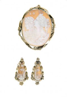 1856 oval-shaped cameo brooch parure.  Profiles of two females carved in white. Earrings of teardrop-shaped cameo for pierced ears. A woman standing in front of a house and tree carved on pink-orange background. The frame is twisted gold with flower-and-leaf motif. Was a Wedding gift of Josiah Shelton Wheeler to Anzonetta Cotton, September 16, 1856.