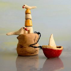 This is a ceramic sculpture, a miniature lighthouse in white and yellow, with a miniature boat and two ceramic birds.    This is a one of a kind handmade