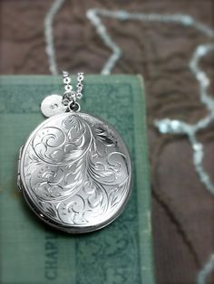 A gorgeous swirl engraved vintage locket boasts a wonderful large size. The locket opens to reveal two places ready to hold your beloved photographs. The back of this locket is stamped with traditional British hallmarks including an anchor for Birmingham, England, a lion passant for solid sterling silver, the date letter B for 1976, and the makers mark NB. The locket is paired with a silver disc charm waiting to be hand stamped with the initial or design of your choice. The locket dangles…