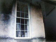 "Savannah Ghost Girl - ""Apparently a little girl died in front of the right window. Look in the bottom of the window. Also there other picture of this window by other sources where the face is captured but in different locations, so it isn't a physical object inside the house."""