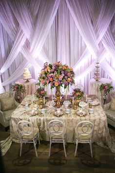 Modern Wedding Reception with Unique Vintage Inspired Furniture and Linens, Tropical Orange, Pink, and Purple Rose with Greenery Centerpieces in Tall Gold Vases, and Drapery with Purple Uplighting