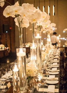 Tall glass vases are lush with white orchids and candles floating inside, complimenting this fabulous wedding table decor. Minus the flames on the candles Tall Wedding Centerpieces, Wedding Table Centerpieces, Wedding Decorations, Centerpiece Flowers, Centerpiece Ideas, White Orchid Centerpiece, Wedding Tables Decor, White Orchid Bouquet, Candle Decorations