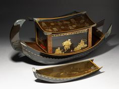 Picnic set in the form of a river boat, made in Tōkyō c.1801-1840 by Kajikawa Bunryūsai. Wood, covered in black nashiji lacquer, with maki-e lacquer decoration in gold, silver, and red; with engraved silver mounts. 33 x 74 x 32 cm max. (height x width x depth)