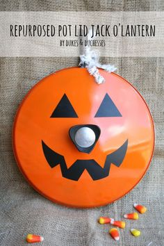 an old thrift store pot lid repurposed into a jack o'lantern