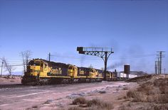 Dalies, NM 2-3-84 - Dalies, NM 2-3-84  Dalies is at the top of the grade out of the Rio Grande valley about 13 miles west of Belen. This train has been audible for several minutes as the 5 big units lift it up onto the plateau.   This is also where the line from Raton and Albuquerque rejoins the Transcon back by the water tower.